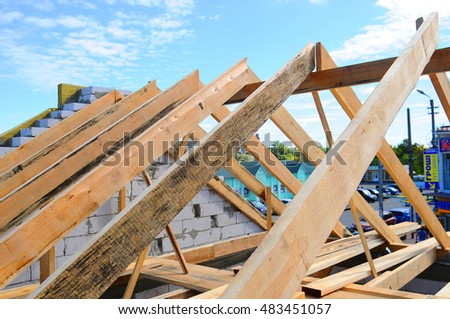 KIEV, UKRAINE - SEPTEMBER 13, 2016: New residential construction home framing against a blue sky. Roofing construction. Wooden construction. installation of insulation wool. white building blocks