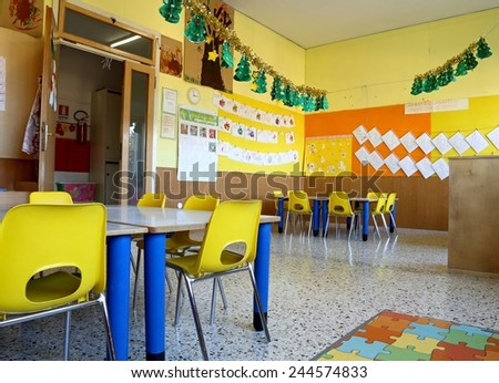 kindergarten classroom with yellow chairs and table  with drawings of children hanging on the walls
