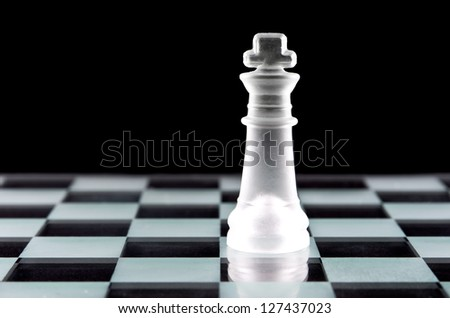 King chess piece on glass chess board isolated on black