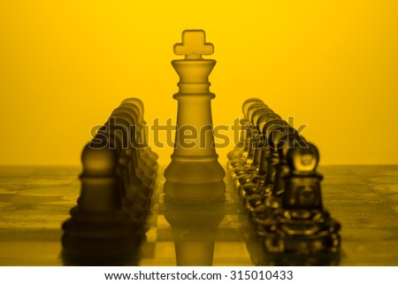 King stands on a chessboard surrounded by pawns
