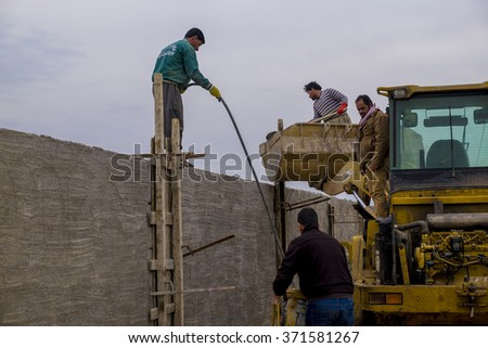 Kirkuk, Iraq - February 2, 2016: Iraqi workers casting concrete on wall to pour the cement inside columns in Iraqi desert