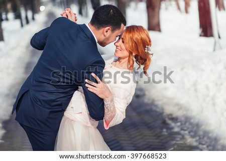 Kiss of bride and groom in winter forest