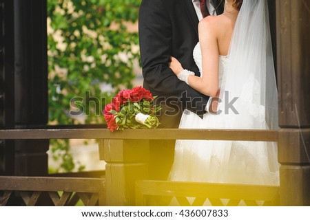 kissing couple at wooden porch with bouquet