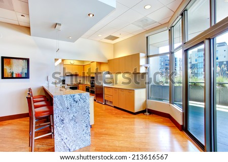 Kitchen room with marble counter top and red stools. View of glass door to walkout deck