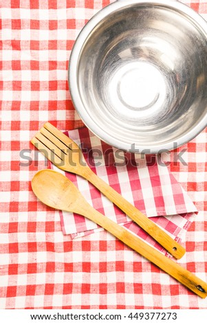 Kitchen utensils on tablecloth on wooden table over