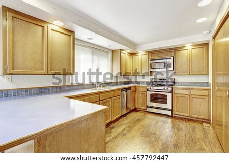 Kitchen With Golden Wood Cabinets And Hardwood Floor. Simple American Home.  Northwest, USA