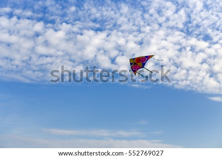 Kite flying in a beautiful sky among the clouds.