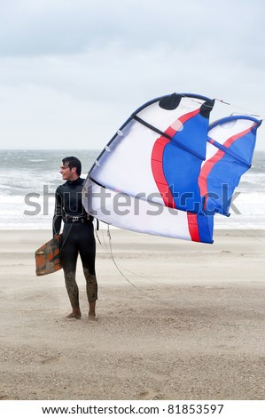 Kite surfer wearing a wetsuit on the beach on a windy day, holding his board and kite, looking sideways