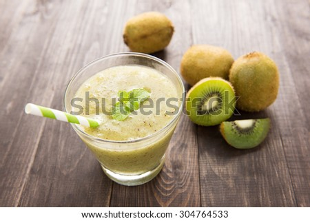 kiwi smoothie with fresh fruits on wooden table.