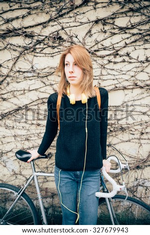 Knee figure of young beautiful hipster sporty blonde woman leaning on her bike, overlooking right, with headphones around her chest - music, sportive concept - wearing black sweater and blue jeans