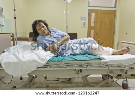 Knee replacement surgery after operation patient senior woman (60s) on the bed in hospital