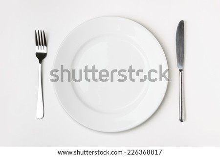 Knife, Fork and plate on table isolated.