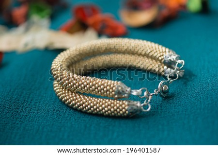Knitted bracelet of gold color from beads