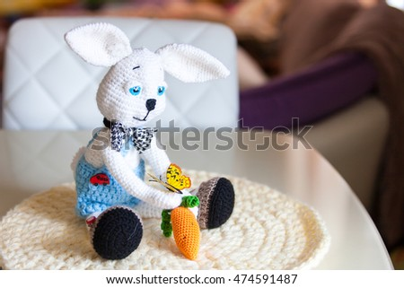 Knitted white Bunny rabbit amigurumi in shorts and a carrot and a butterfly is sitting on the table