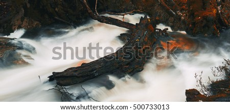 Knyvet Falls in Cradle Mountain, Tasmania after heavy rainfall with abstract red hues added.