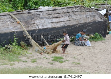 Kochi, India - November 1, 2015 - Homeless family sitting near boat on beach of Kochi, India