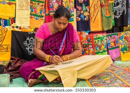 KOLKATA, INDIA - NOVEMBER 28: An Indian craftswoman paints on colorful handicraft items for sale during the annual State Handicrafts Expo 2015 on November 28, 2015 in Kolkata, West Bengal, India.