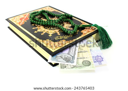 Koran with Egyptian banknotes in front of white background