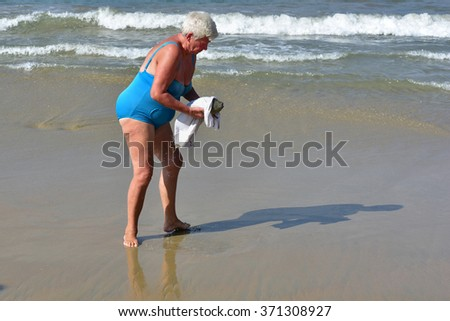 KOVALAM, TRIVANDRUM, KERALA, INDIA, FEBRUARY 02, 2016: Rescuing a puffer fish. An old female tourist picks up a pufferfish that was caught in the net of fishermen, and takes it to the sea.