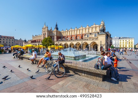KRAKOW, POLAND - September 16, 2016: Tourists enjoying an summer day in The Grand Central Square in front of the The Renaissance Sukiennice also known as The Cloth Hall, Krakow, Poland