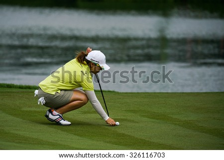 KUALA LUMPUR, MALAYSIA - OCTOBER 09, 2015: Japan's Mika Miyazato lines her putt at the 18th hole green at the KL Golf & Country Club at the 2015 Sime Darby LPGA Malaysia golf tournament.