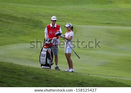 KUALA LUMPUR - OCTOBER 13: Beatriz Recari of Spain selects here club for her next play at the KLGCC course on the final day of the Sime Darby LPGA on October 13, 2013 in Kuala Lumpur, Malaysia.