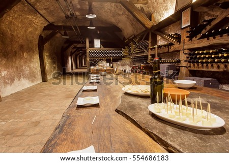 KVARELI, GEORGIA - OCT 3: Table with cheese and wine glasses winside the tasting room of old cellar Khareba Winery on October 3, 2016. The cellar tunnel was opened in 1962 for the World Wine Congress