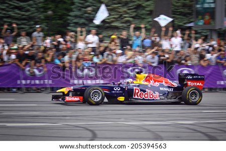 KYIV, UKRAINE - MAY 19, 2012: Daniel Ricciardo of Red Bull Racing Team drives RB7 racing car during Red Bull Champions Parade on the streets of Kyiv city