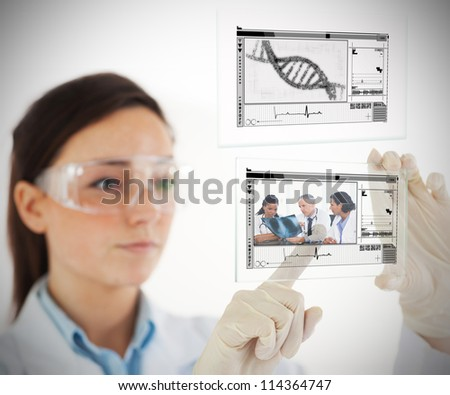 Lab technician selecting medical image from hologram interface on white