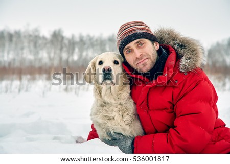 Labrador retriever dog for a walk with its owner man in the winter outdoors