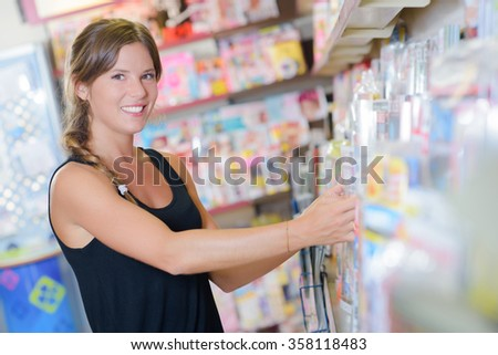 Lady arranging magazines on shelf in newsagents