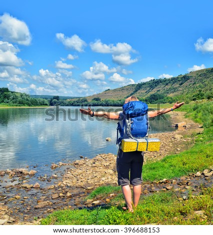 Lady hiker standing on the grass and enjoying view of the river