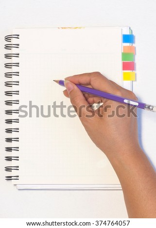 Lady's hand holding pencil ready to write an empty notebook with sticky note memo