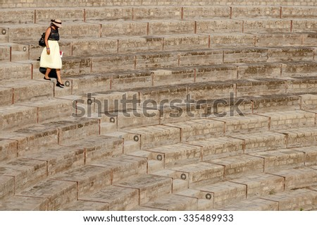 Lady walking down  steps at large theatre in Pompeii, Italy. Pompeii was destroyed and buried with ash and pumice after Vesuvius eruption in 79 AD.