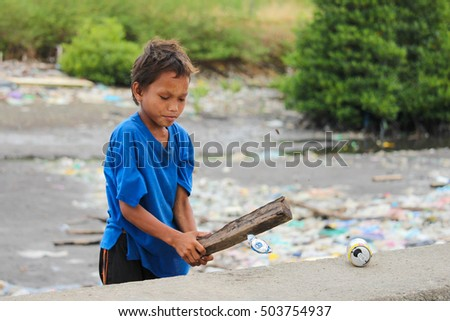 LAHAD DATU, SABAH MALAYSIA- SEPT 05, 2016: A Pala'u kid smashes discarded cans using wood. Collecting cans is one way to make a living for Pala'u community or Sea Gypsies that reside on the waters