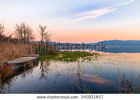 Lake Comabbio in autumn at sunset. On the background Varano Borghi; province of Varese, Italy
