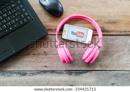 LAMPHUN,THAILAND - NOVEMBER 2,2015:Brand new Apple iPhone 4s with Youtube app on the screen lying on wood with pink headphones,YouTube is the popular online video-sharing