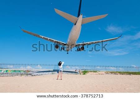 Landing airplane at the airport nearby the beach with people in a clear blue sky day in Phuket, Thailand, Selective focus