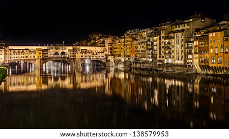 landscape at night of Florence, Italy: view of the famous landmark Ponte Vecchio (old bridge), a medieval bridge over the Arno river