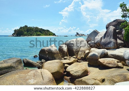 Landscape of a beach fulled with giant boulder of granite stones.