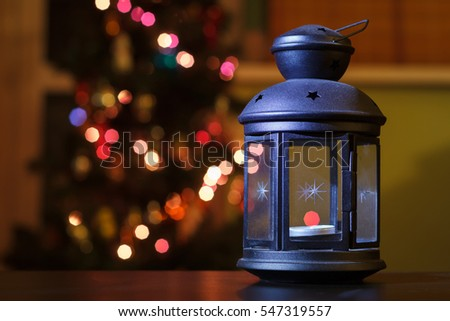 Lantern on a background of holiday lights. Christmas card. Holiday lantern on the bright blurred Xmas lights background, space for your text, copyspace