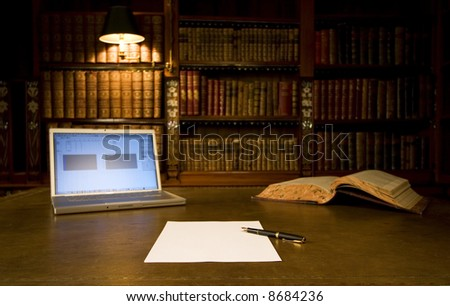 Laptop in classic library with blank sheet of paper and pen series