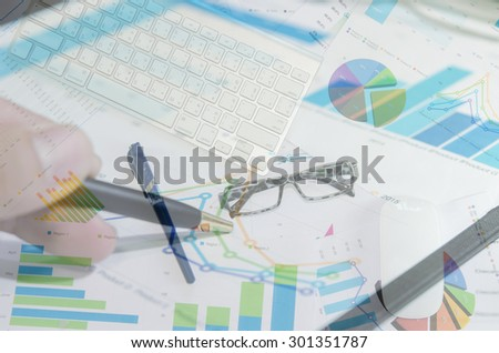 laptop, over papers with numbers and charts. business Concept