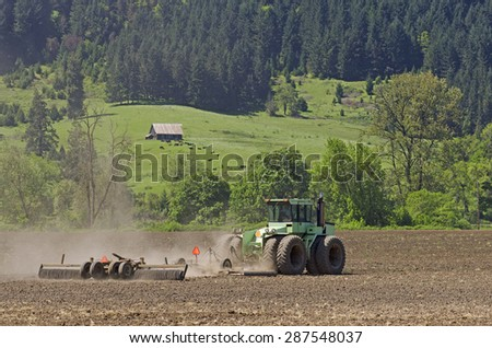 Large agricultural tractor smoothing out a tilled field with a disc implement preparing for planting