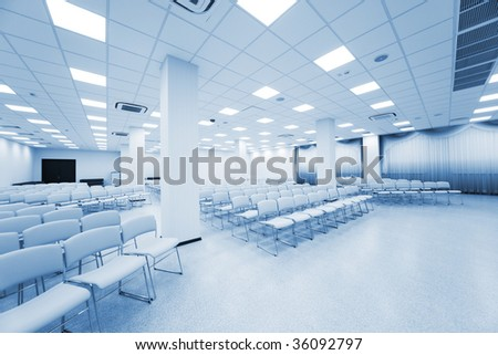 large and modern white auditorium with blue curtains