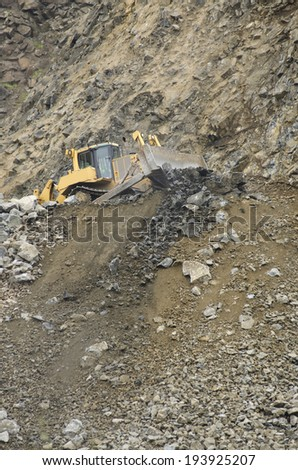 Large bulldozer moving large rocks to feed a rock crusher at a rock pit for gravel
