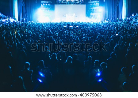 Large concert hall filled with spectators before the stage.