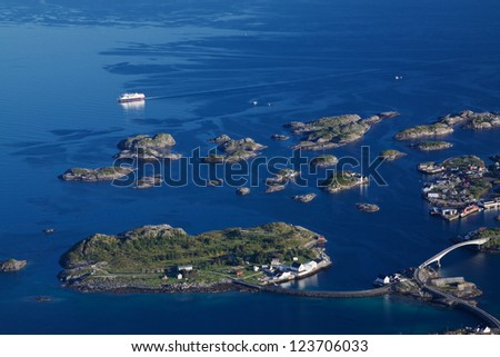 Large cruising ship passing by picturesque tiny islands on norwegian coast connected by bridges near town of Henningsvaer on Lofoten islands