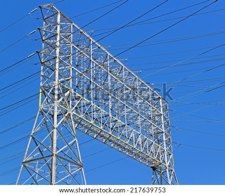 Large industrial electricity transmission tower or electricity pylon steel lattice grid structure, close up view.