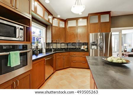 Large kitchen room interior with brown cabinets and modern stainless steel appliances. Northwest, USA